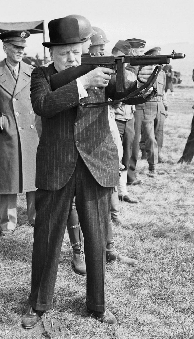 Winston Churchill squints as he test fires an American M1928 Thompson submachine gun, many of which were supplied to England under the Lend-Lease program. Note the unusual hybrid forestock with both descending pistol and horizontal hand grips.