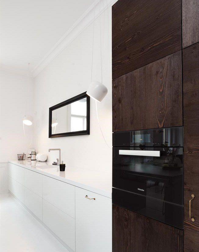 """Na nízkou sestavou skříněk s dřezem je zrcadlo, prostor opticky rozšiřuje a potlačuje i """"kuchyňský charakter""""."""