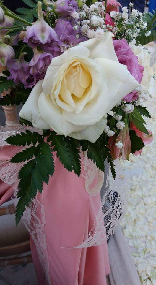 flower arrangement at the back of the chair. Chair's decoration at the ceremony. Cleopatra's weddings -  wedding planner in Greece