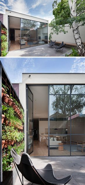 Summer style!! Modern contemporary landscaping and home! In this modern courtyard, a high wall and black fence provide privacy from the neighbors. A built-in bench and a couple of outdoor chairs create spaces to relax, and built-in planters and a wall of potted plants add a touch of nature. #Landscaping #Courtyard #PlantWall #Windows