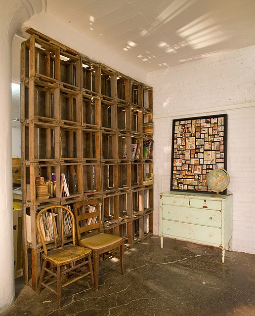 crates are used as a dividing wall and bookshelf