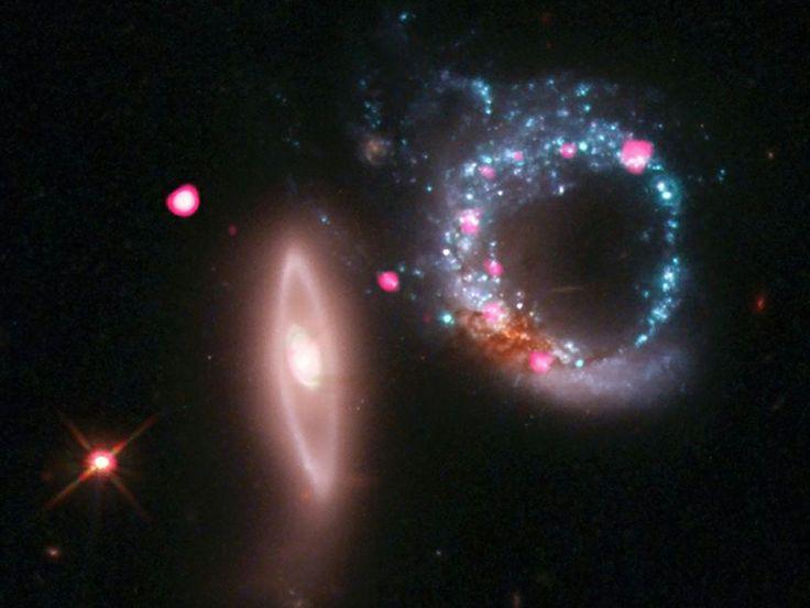 Image Credits: X-ray: NASA/CXC/MIT/C.Canizares, M.Nowak; Optical: NASA/STScI|ブラックホールの指輪、Arp 147:指輪のように輝く青い渦巻銀河。左の楕円銀河とペアになり、衝突銀河Arp 147を構成している(合成画像)。リング上の青色は若い大質量星で、ピンク色はブラックホールが発するX線である。  ハッブル宇宙望遠鏡が可視光で撮影した多数の大質量星は、左の楕円銀河が渦巻銀河を突き抜けた衝撃で...