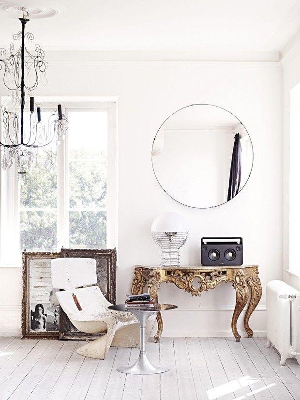 Sala branca com móveis dourados e ecléticos