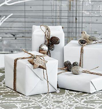 Inpakidee voor Kerst: wit papier met een eenvoudige versiering.