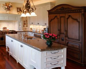 refrigerator and freezer are built in to a custom wood surround that looks like traditional wood furniture.