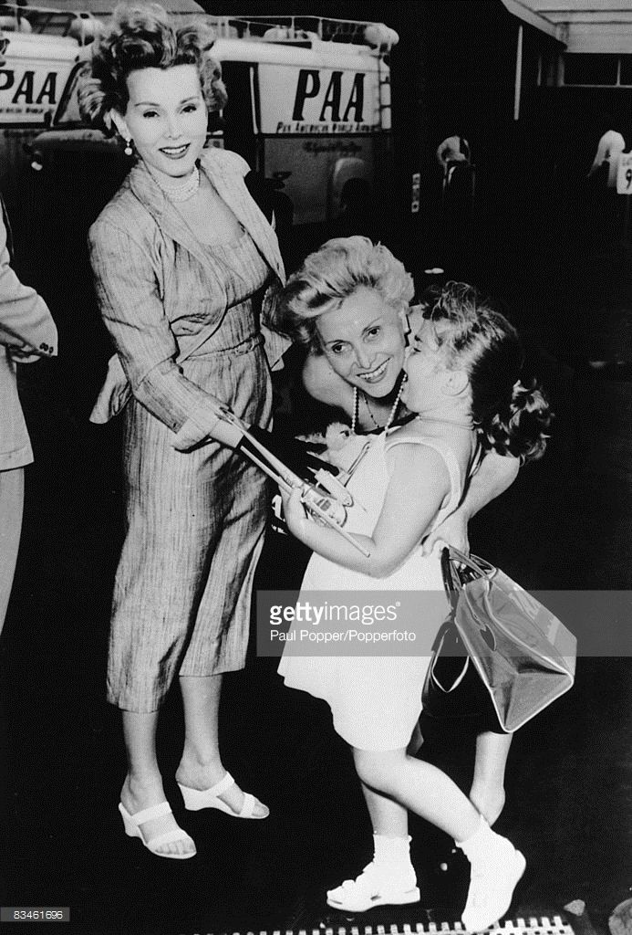 Hungarian actress Zsa Zsa Gabor (left) looks on as her mother Jolie Gabor (1896 - 1997) says goodbye to Zsa Zsa's daughter Constance Francesca Hilton at John F. Kennedy Airport, New York, 31st July 1953.