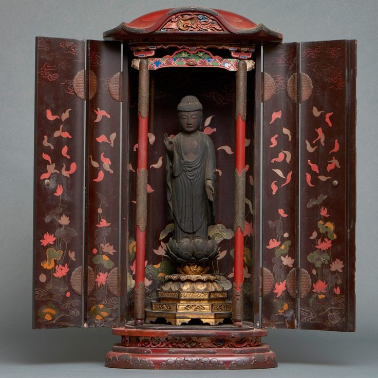 A  dark red lacquered wooden zushi-shrine, its black lacquered inside decorated with a lotus pond with white and red lotus flowers and lotus leaves in gold maki-e lacquer. With decorative metalwork. The shrine has a black wooden Raikō Amida (Amitabha) with his left hand the vitarka-gesture or the raiko'in gesture of welcoming the souls of…