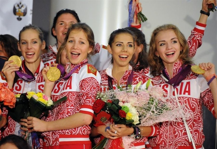 Athletes from the Russian Olympic national team smile and hold up their gold medals after arriving home at Sheremetyevo international airport in Moscow, Russia, on August 13, 2012.
