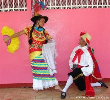 """Perú: Influencia española en las vestiduras del pueblo. Mujer con falda colorida y lentejuelas pegada al cuerpo, que es también conocido como """"traje de india lujosa""""; ésta se acompaña con un sombrero coronado con arreglos de plumas y un abanico también de plumas. El hombre camisa blanca, con capa oscura decorada con lentejuelas, sombrero con el ala doblada al frente y con una flor roja,más varias tiras de colores que caen hacia atrás, y un pantaloncillo embombado, medias blancas y…"""