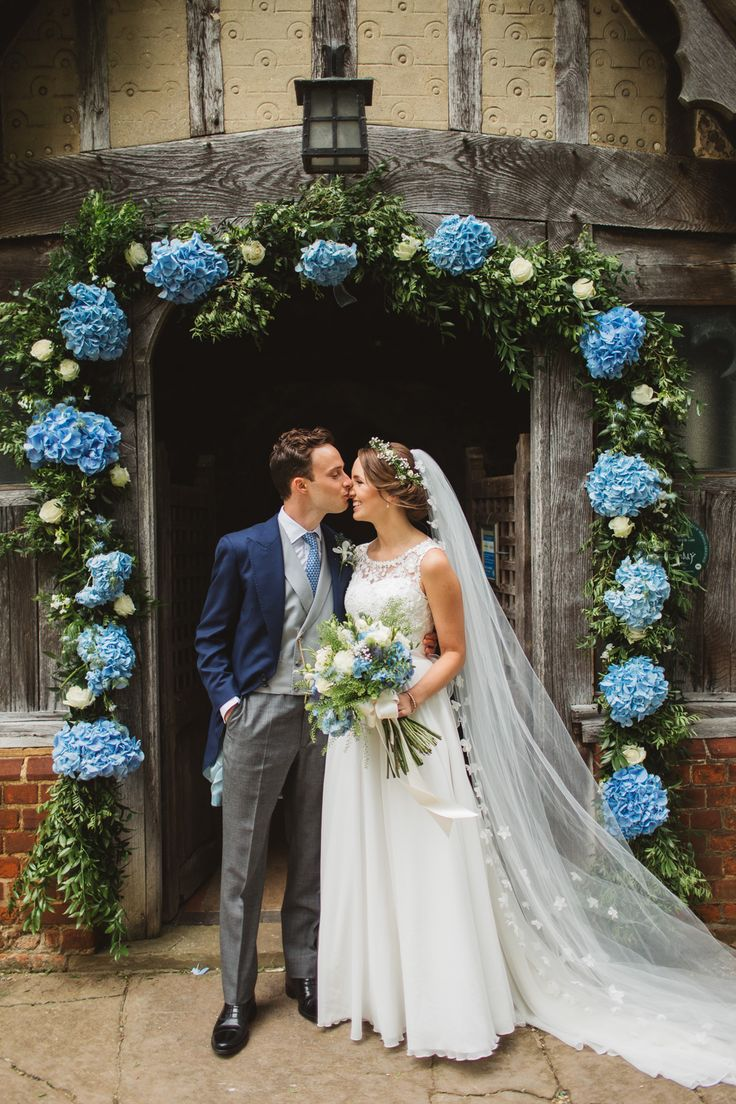 Blue Hydrangea Church Floral Arch - Frances Sales Photography   Rustic Wedding at High House Weddings in Essex   Lace Ingrida Bridal Gown   Pale Blue For Her and For Him Bridesmaid Dresses   White & Blue Hydrangea Flowers