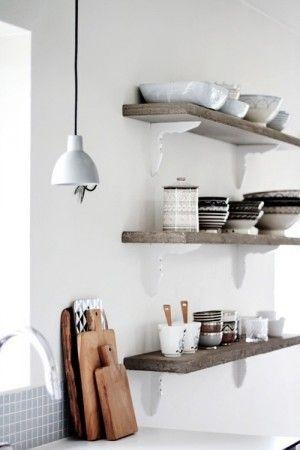 Naturelkleurige planken op witte plankdragers met mooie accessoires.