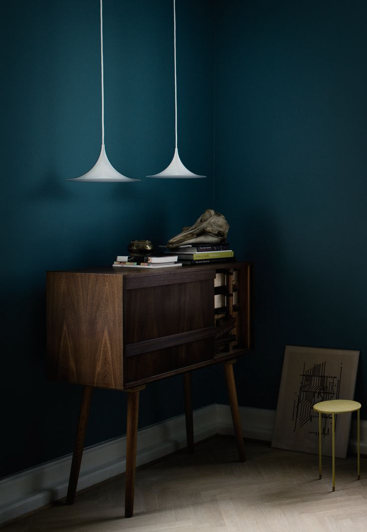 A pair of GUBI Semi Pendants lightens up the dark hues in this stylish corner.