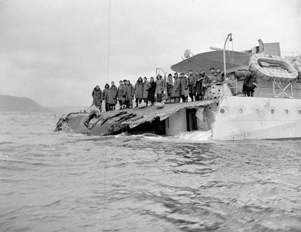 HMCS SAGUENAY (D79) crew contemplate their future  Damaged stern of the destroyer HMCS SAGUENAY (D79).   HMCS SAGUENAY (D79) was rammed by S.S. AZRA south of Cape Race, and lost her stern when her depth charges exploded in St. John's, Newfoundland on November 15, 1942.  The destroyer could not be made seaworthy and was later used as a training ship.  Photo by John D. Mahoney. Department of National Defence / National Archives of Canada, PA-153500.