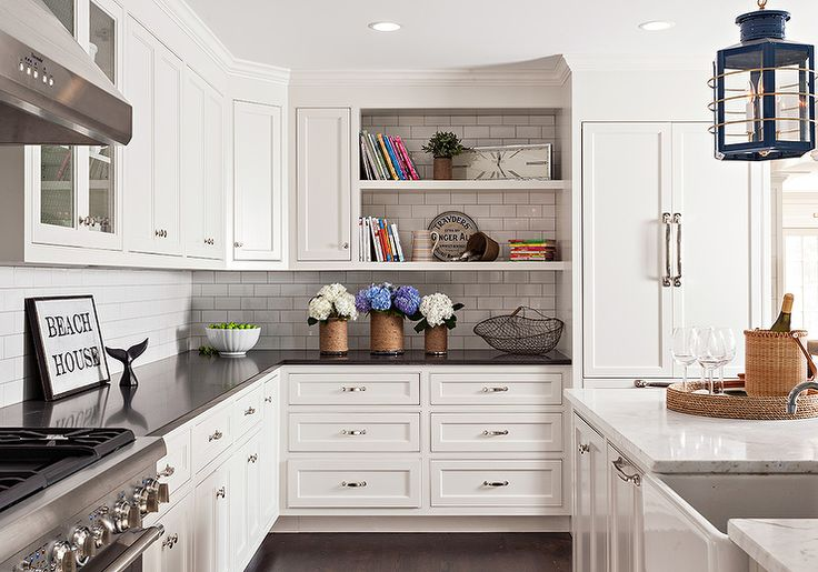 Beautifully designed two tone kitchen features walls lined with white shaker cabinets fitted with polished nickel knobs and black quartz countertops accented with a white subway tile backsplash and positioned beneath upper cabinets finished with open shelves located beside a white paneled refrigerator.