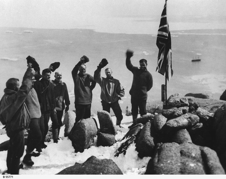 "GENERAL: Men of the B.A.N.Z. Antarctic Research Expedition, 1929-31, grouped around a Union Jack flag, cheering and holding their hats in the air. According to a researcher, this is at Proclamation Rock or Island. BANZ or BANZARE was at Proclamation Rock or Island on Monday 13th January, 1930. From Eric Douglas's log ""...8am In clear water now about 1/4 mile off this rock which appears about 700 ft high. 9am A party left in the motor boat (ten of them) their main job being to hoist the flag…"