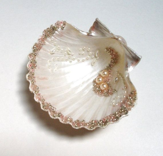 This lovely ring bearer shell has a white pearlescent finish and is hand decorated with white and pink glass pearls. I have beaded her scalloped edge and a small pattern in the bowl of the shell with a mix of ice pink and silver lined Czech glass beads and white pearls. Two silvered shell feet keep this little beauty upright. This beautiful scallop holds rings, earrings and other small objects in style. This shell would be a fabulous way to present an engagement ring or other jewelry. She…
