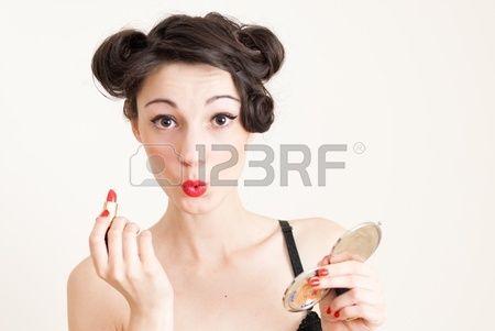 Grappig mooi gelukkig pin up meisje met rode lippenstift en handspiegel Stockfoto
