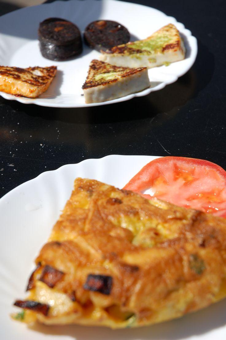 Ziemniaczany hiszpański omlet. A w tle pyszna teneryfiańska kaszanka na słodko z migdałami oraz świeży ser z grilla w sosach mojo.