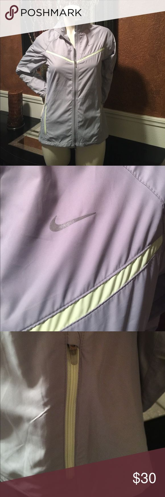 Women's Nike water repellent wind breaker In perfect condition. Semi-fitted.  Light gray with a light yellow stripe across the chest and outlining the zippers.  Vented back. Nike Jackets & Coats