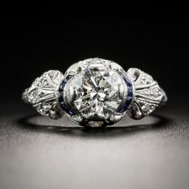 A bright white and blazing transitional-cut diamond, weighing 1.00 carat, sizzles night and day from within this distinctive Art Deco dazzler, die-struck an hand-finished in platinum - circa 1930. The scintillating stone is accented on each side with a narrow scroll of royal blue calibre sapphires, followed by dimensional, diamond-set bow motif shoulders. Decorative hand-engraving adorns the top of the ring shank and side gallery. Unique, chic and magnifique! Currently ring size 5 1/4.