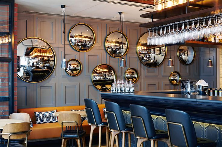 PURO Hotel, Gdańsk. Panelled wall combined with large round mirrors makes a dramatic statement in this funky bar. Black bar stools and detail on the bar front add an air of luxury.