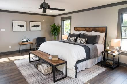 Yet another wall was removed in order to merge two bedrooms and create an enlarged master suite. Joanna maintained the earthy and masculine aesthetic with dark wood floors, contrasting tones, gray walls, plenty of wood and a pair of framed prints based on vintage fishing-lure designs.