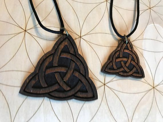 You may choose the small or large pendant. Please see photos for size. This is a wooden Triquetra pendant with an adjustable parachord necklace. It is made out of birch wood, stained dark and is made to order. Please allow up to 5 business days for production. The triquetra (sometimes, triqueta) is a tripartate symbol composed of three interlocked vesica pisces, marking the intersection of three circles. It is most commonly a symbol of the Holy Trinity (Father, son, Holy spirit) used by the…