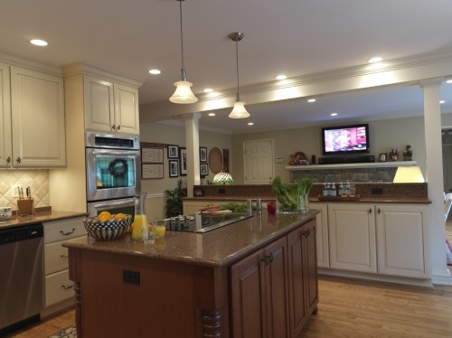 Island With Bar Top And Flanked By Columns Looking Towards Tv In The Living Room