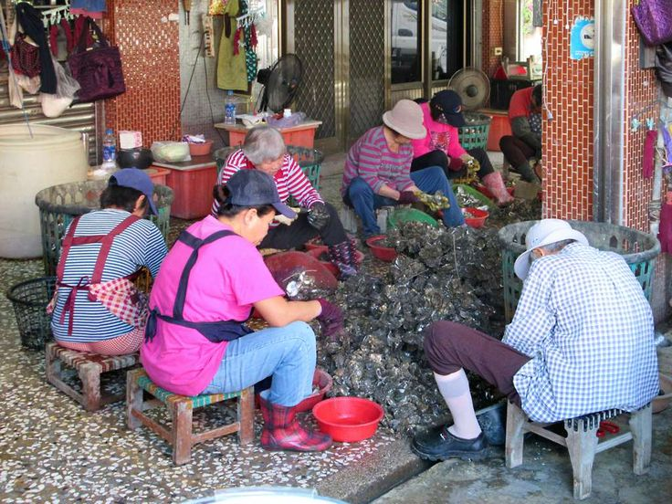 These Chinese workers are shucking oysters on Anping Road in Tainan, Taiwan.