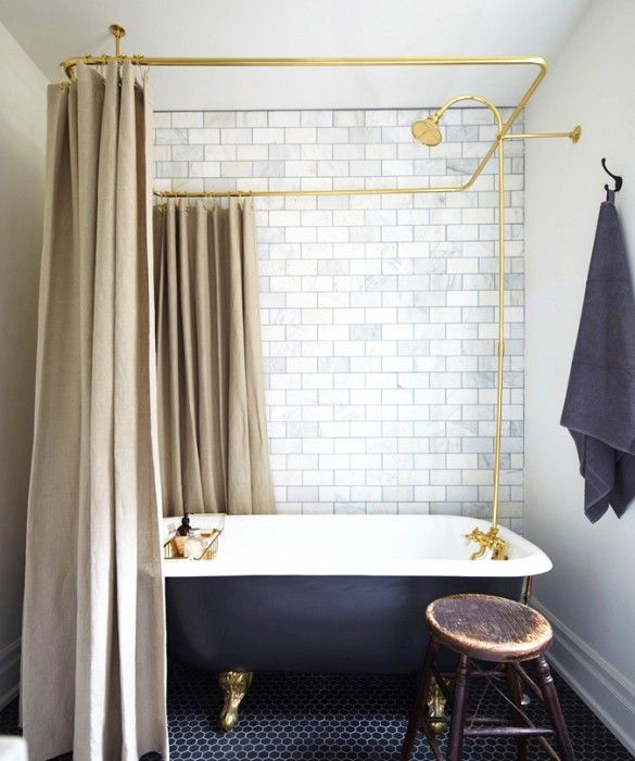Two types of tiles in neutral bathroom with navy tub and taupe curtains