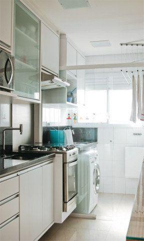Para aproveitar na cozinha a luminosidade que vem da área de serviço, o casal separou os ambientes com uma porta de correr de vidro. Cada vareta do varal sobe e desce individualmente, facilitando a tarefa de pôr as roupas para secar.