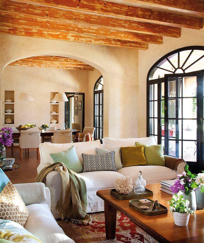 Salón con sofás blancos y comedor al fondo