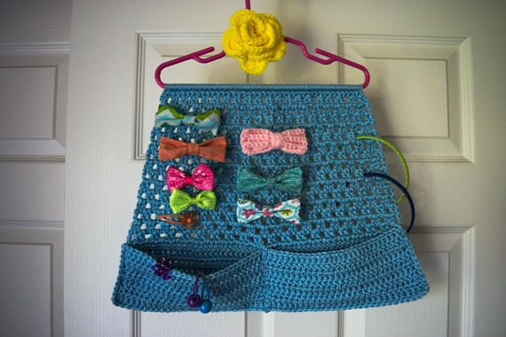 Customize your little girls own hair bow organizer by choosing the colors for the organizer & the rose flower! This crochet wall hanging is the perfect storage for all those hair bows, barrettes and headbands that she likes to wear. It comes with two wide pockets to hold various rubber bands and hair ties (the wide pockets allow her hand to easily rummage for them). This holder looks like a little skirt with pockets, and would be a cute addition to your little girls room. Note: This item ...