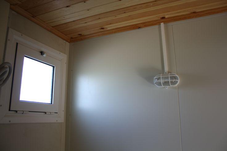 Κοντινό πλάνο από το εσωτερικό του δωματίου που προορίζεται για χρήση W.C. Διακρίνεται το μικρό παράθυρο και η χελώνα φωτισμού.