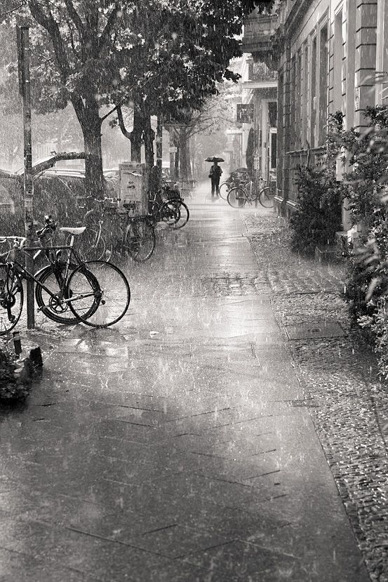 Love everything about this...the rain, the perspective leading up to the figure with the umbrella..THE BIKES ❤