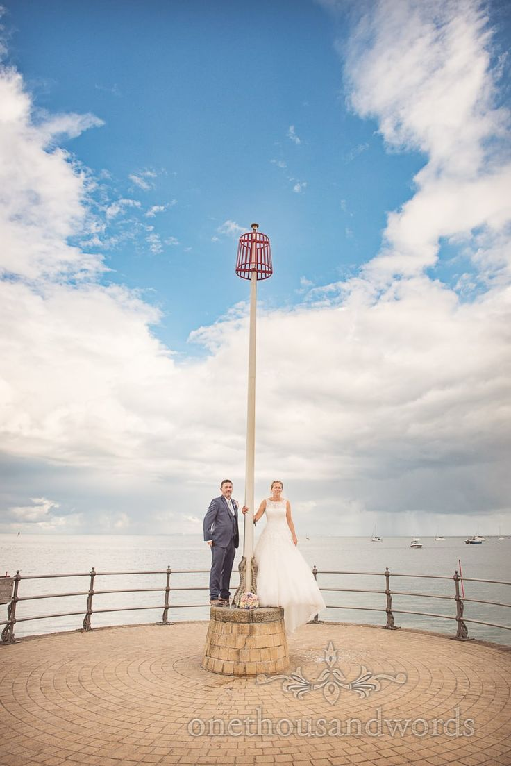 Bride and groom on Swanage stone pier with pole and rain clouds over the sea.Photography by one thousand words wedding photographers