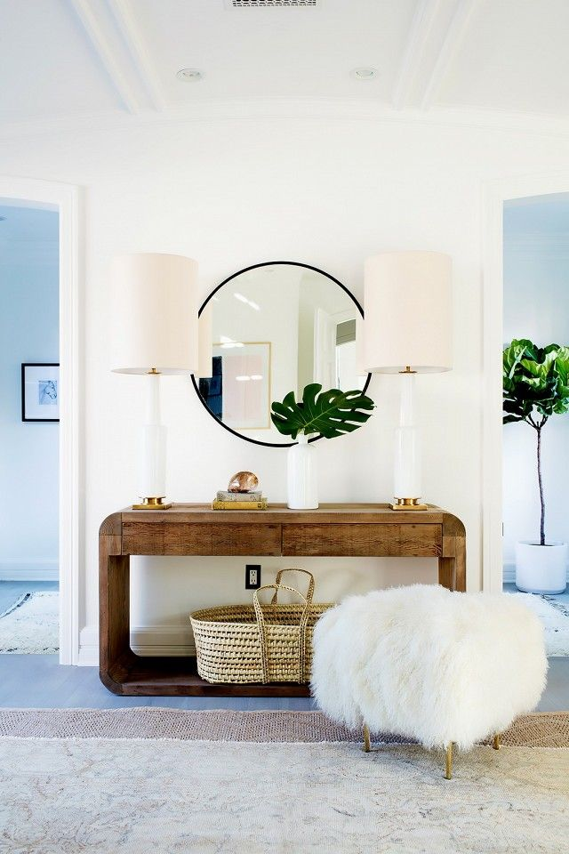 Living space with a wooden dresser, matching lamps and a round mirror