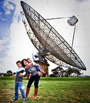 Adult and two children playing on the grass in front of the Parkes radio telescope (Image: Mark James Photography and Parkes Shire Council)