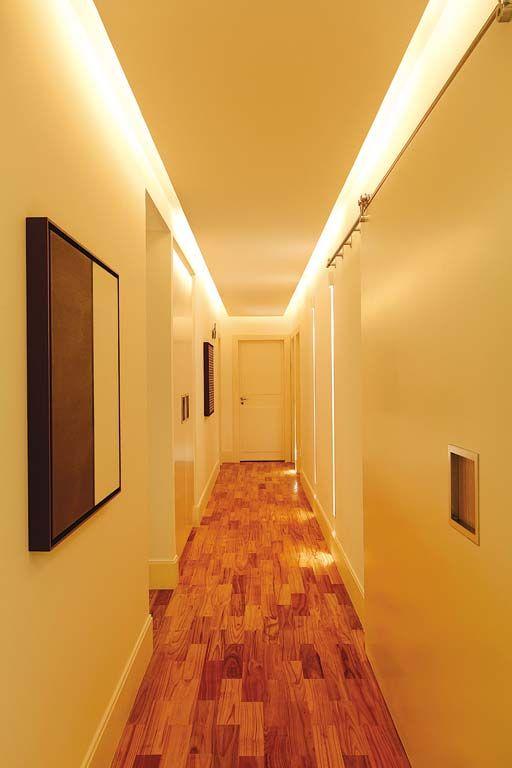 """""""A sanca, descolada 10 cm da parede, esconde fluorescentes T5 de 28 w, eficientes e duráveis. Usados como balizadores, os dois rasgos criados na parede com luminárias da Prolight encontram-se a 45 cm do piso. Os recursos luminotécnicos funcionam em circuitos independentes, o que permite acionar um por vez."""""""