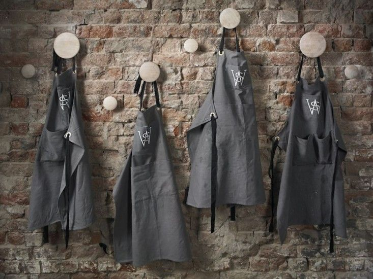 Gray aprons hang on natural wood finish Muuto circular coat hooks with exposed brick wall background inSuper Whatnot in Brisbane Australia, Marc and Co, Alicia Taylor | Remodelista