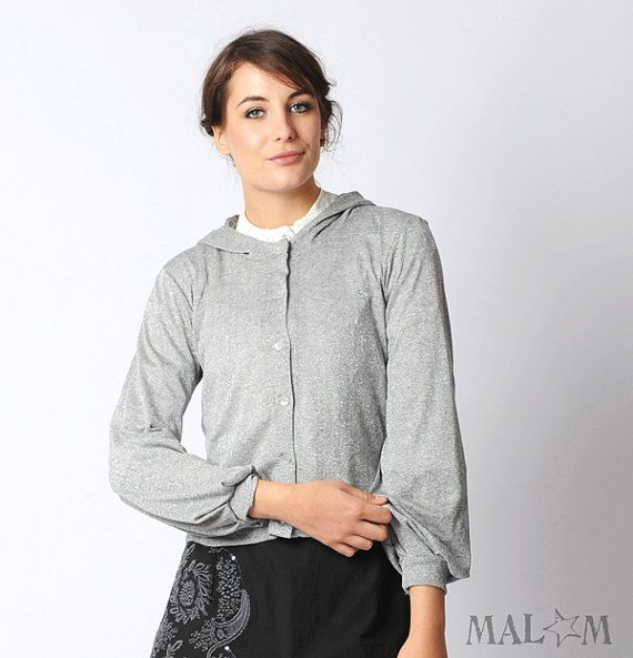 Handmade hooded cardigan in thin silvery grey knit. It has long sleeves, gathered at the wrist, and a wide hood lined with thin grey jersey.    Closes