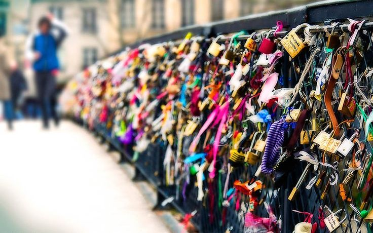 LOVERS BRIDGE IN PARIS - lovers fasten padlocks to the railings of the Pont des Arts bridge in Paris. The couple then toss the keys into the Seine river below, symbolizing their eternal love...