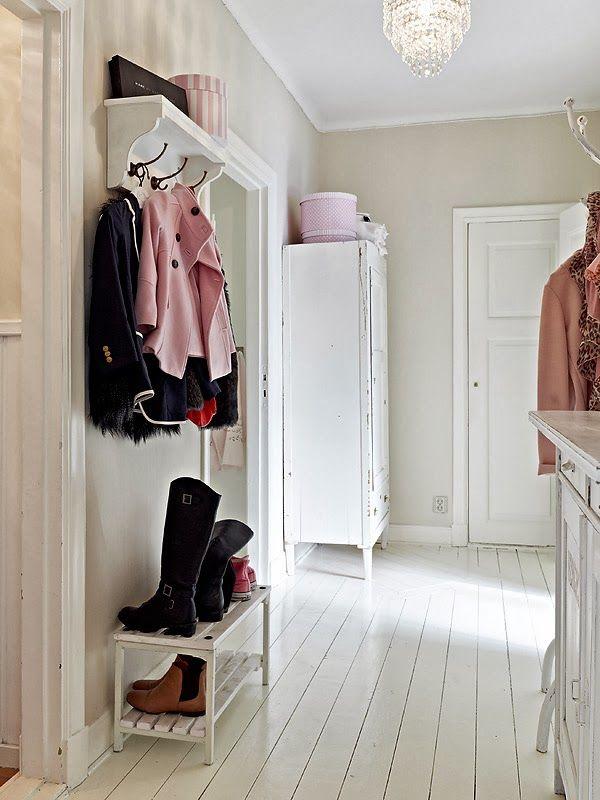 White coat rack/shelf with distressed white wood shoe bench beneath.