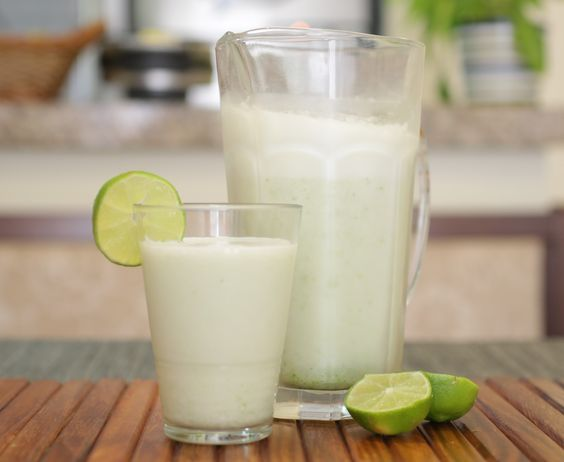 Corte o limão em cruz e retire a parte branca dele, pois é essa parte que amarga. No liquidificador, coloque a água, o limão com a casca e bata bem. Acrescente o leite condensado aos poucos e depois bata por mais 20 segundos, para a limonada...