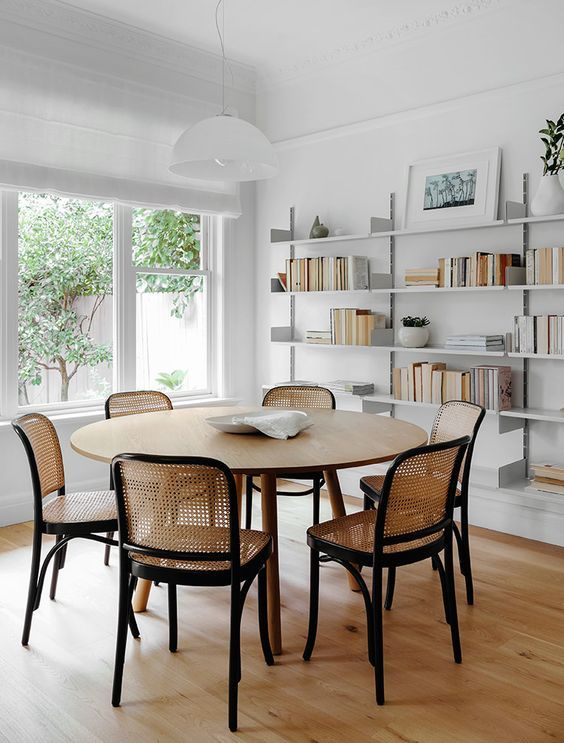 Love the unexpected cane back chairs in this dining room. They imperfectly match the table. The shelves seem forced....like it's a rental house and you can't take them down though. I'd do a mid tone midcentury book case or two raw edge floating shelves would be amazing