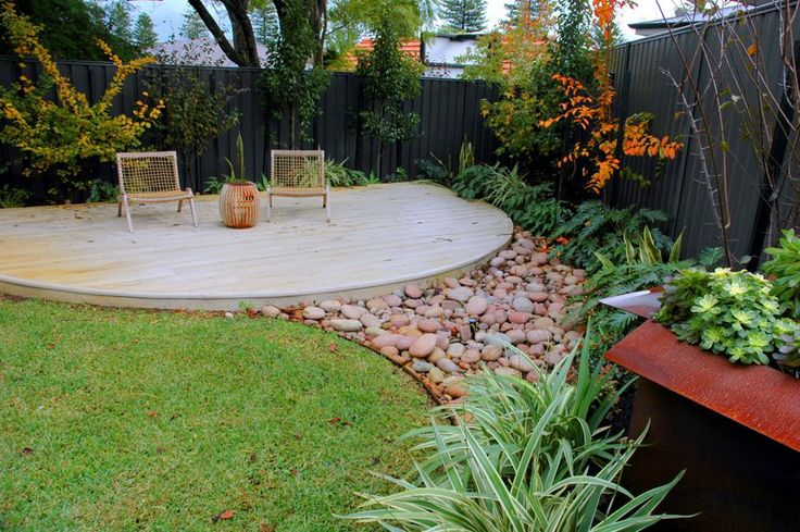 Inviting sitting area next to concealed water feature with riverstones #water features