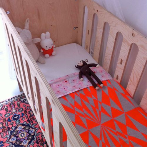 interesting blanket and rug. i like the stuffed animals too. look at the simplicity of the wooden crib.