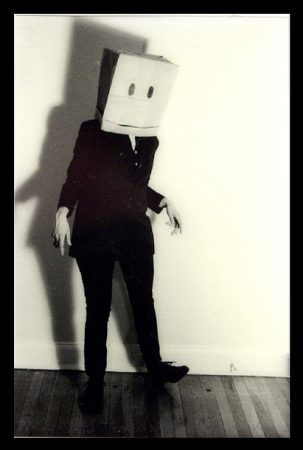 A stronger black-and-white tone photo, the shadowing and lighting creating a highlight and a alternate-version of the subject.  paper bag head by BSmaurer, via Flickr
