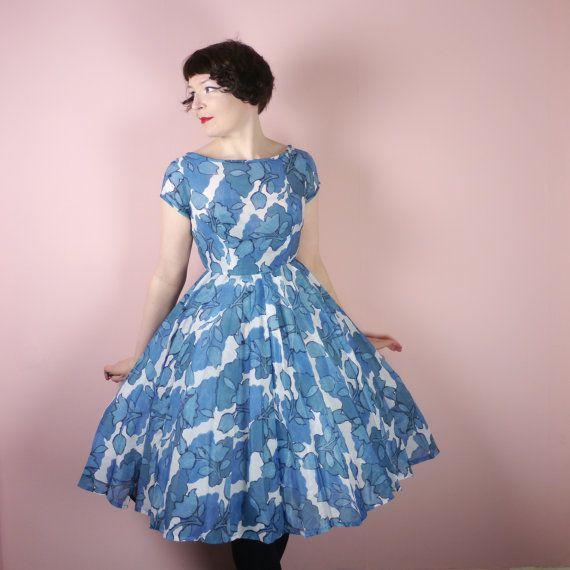 Drucken Sie flirty wenig Sommer Kleid in weiß und hell blau floral. Es ist etwa Anfang der 60er Jahre Ära, aber der Schnitt ist noch sehr der 50er Jahre inspiriert, mit einem vollen Faltenrock und sehr erstickt in Taille. Oberteil ist mit kurzen Ärmeln und Rundhalsausschnitt und V-Rücken ausgestattet. Stoff ist ein leichtes synthetisches, sehr leicht schiere. Es fühlt sich ein bisschen wie ein Baumwolle-Imitation, könnte möglicherweise eine Baumwoll-Polyester-Mischung, es hat eine etwas…