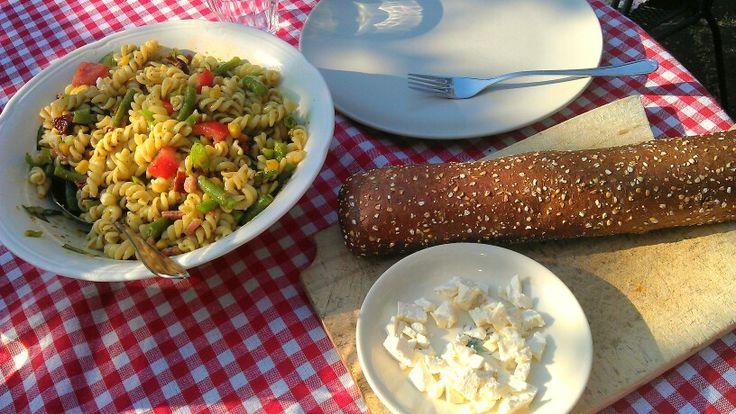 Zomerse maaltijd. Koude pasta met boontjes, lente ui, tomaat, pesto, spekjes en fetta. En bruin stokbrood